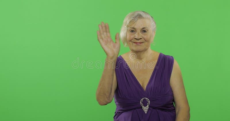 Пожилая женщина развевая к камере и улыбкам Старая бабушка o стоковые фото