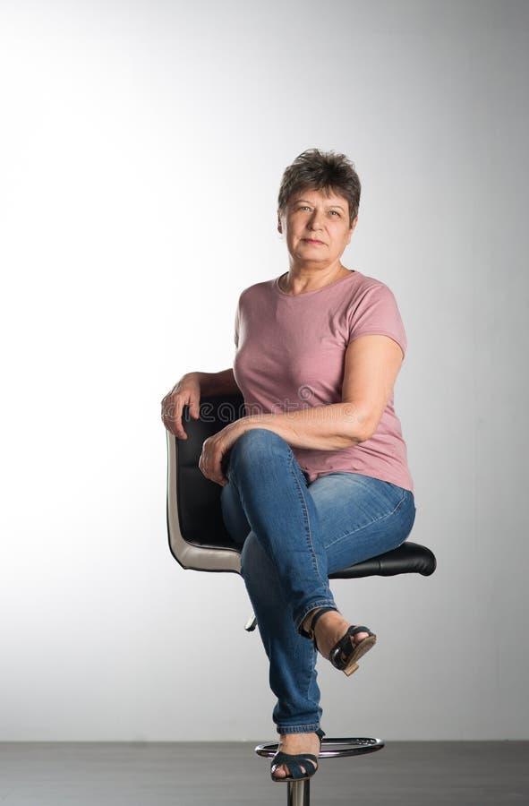 Пожилая женщина сидя на стуле стоковое изображение