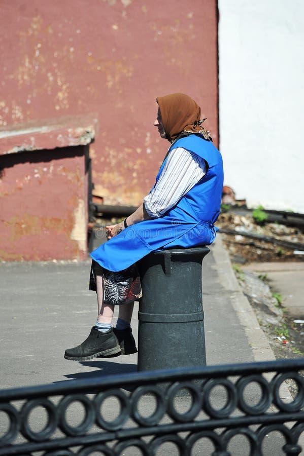 Пожилая женщина - старый бездомный человек сидя в старое worn-вне стоковое фото