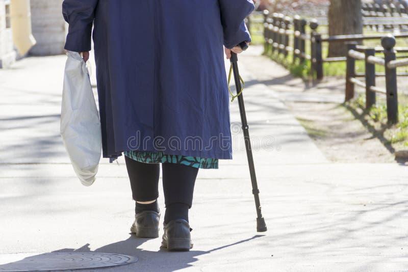 Пожилая женщина с тросточкой и пакетом идет на квадратный путь стоковые изображения