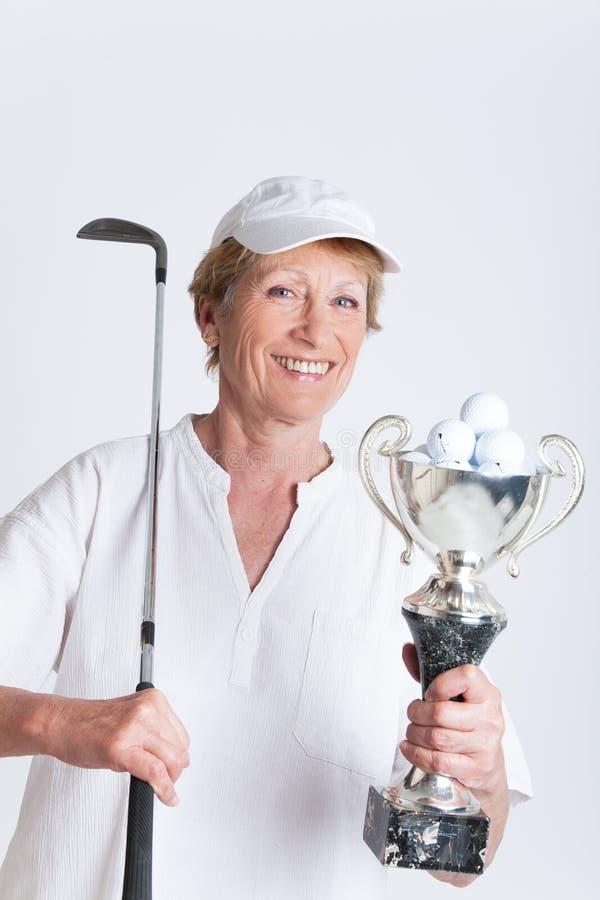 Пожилая женщина с трофеем гольфа стоковое изображение