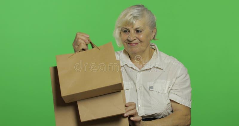 Пожилая женщина с хозяйственными сумками : presents o стоковое изображение