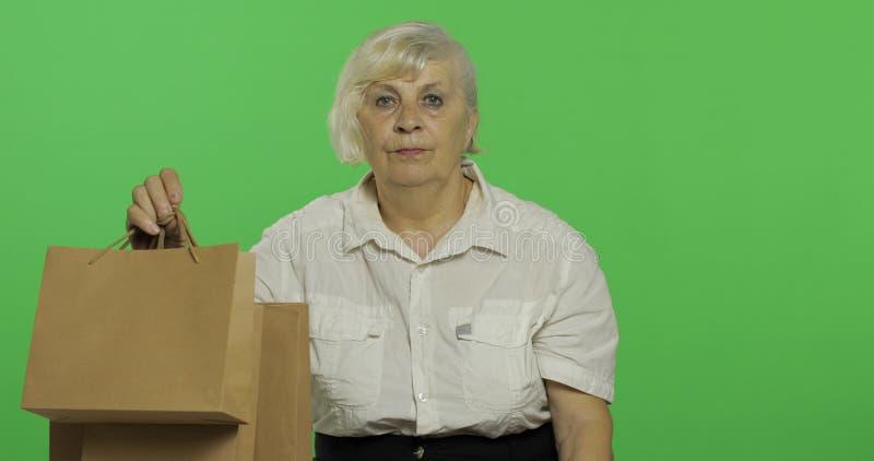 Пожилая женщина с хозяйственными сумками : presents o стоковое фото rf