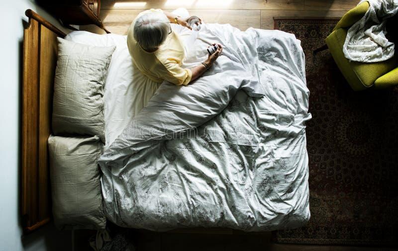 Пожилая кавказская женщина просыпая вверх стоковое фото rf