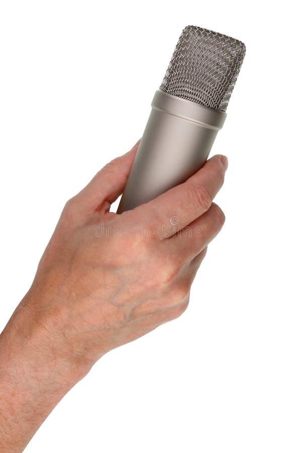 Пожилая мужская певица держит вокальный микрофон конденсатора в его руке стоковые фотографии rf