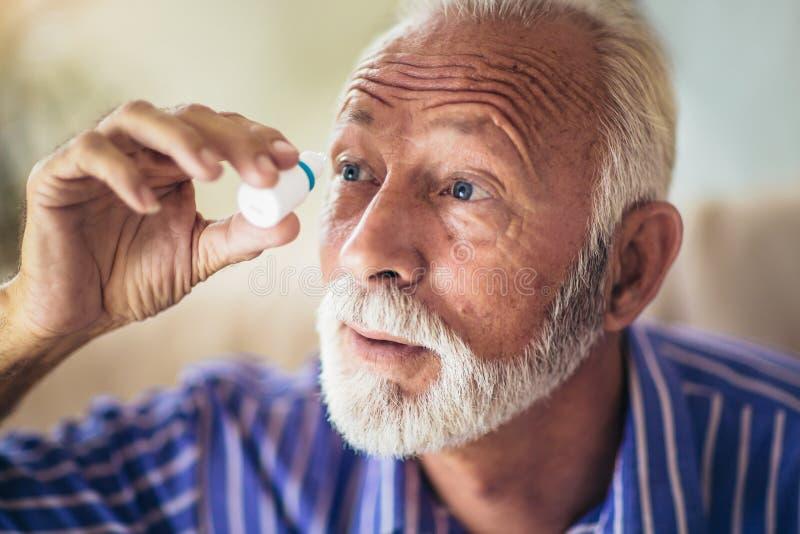 Пожилая персона используя падения глаза стоковые изображения