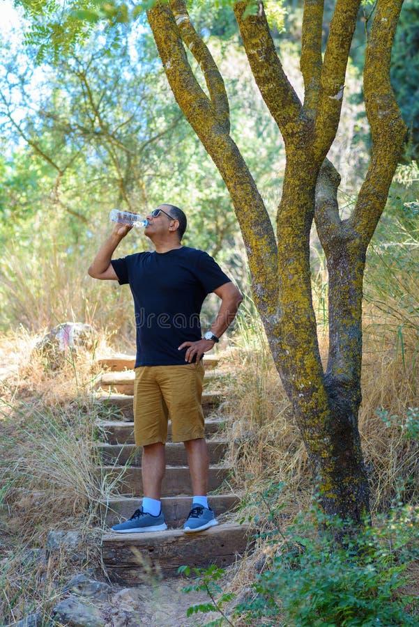 Пожилая питьевая вода старшего человека спортсмена успеха после отключения стоковые изображения