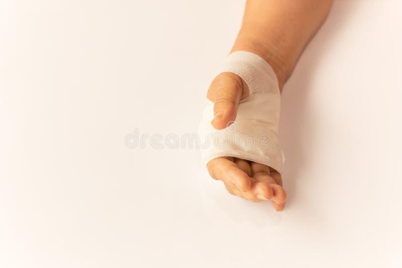 Пожилая рука женщины поврежденная с повязкой на белой таблице в больнице стоковое изображение
