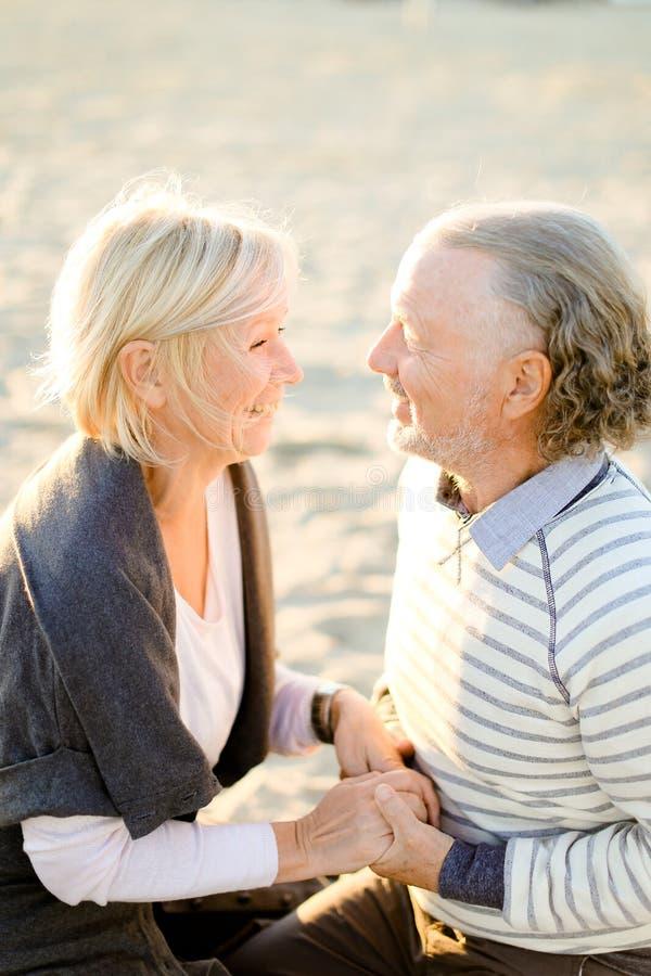 Пожилая усмехаясь жена держа супруга рук старшего и сидя на пляже песка стоковые изображения rf