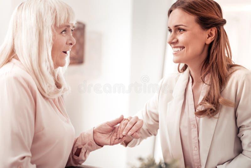 Пожилое положительное усмехаясь белокурое чувство женщины шикарное стоковое изображение rf