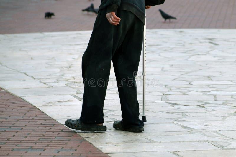 Пожилой бедный человек идет с тросточкой вниз стоковые фотографии rf