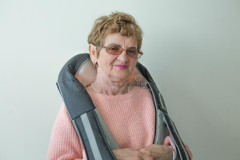 Пожилой кавказский портрет плеч прибора massager женщины стоковое фото