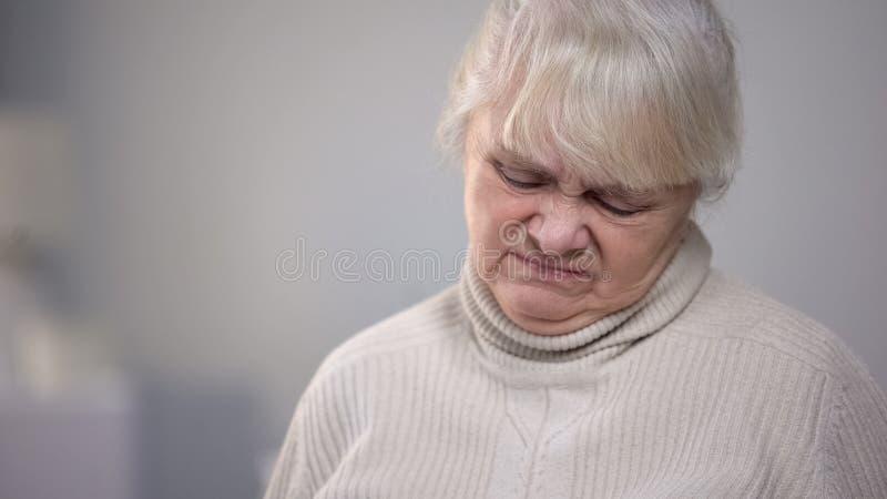 Пожилой конец-вверх стороны женщины с опостылеть выражением, проблемой здоровья слабоумия стоковая фотография rf