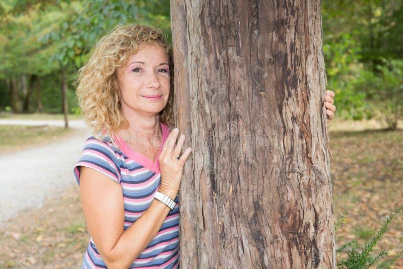 Пожилой портрет женщины внешний в парке около дерева стоковое фото