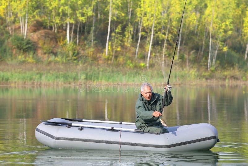 Пожилой рыболов как раз уловил рыбу стоковое изображение