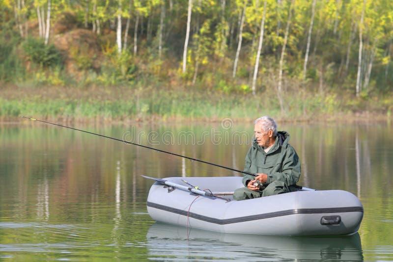 Пожилой рыболов удя от его шлюпки на солнечный день осени стоковые изображения