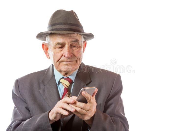 Пожилой старший человек в ретро шляпе используя его мобильный телефон изолированный на белой предпосылке стоковое фото rf