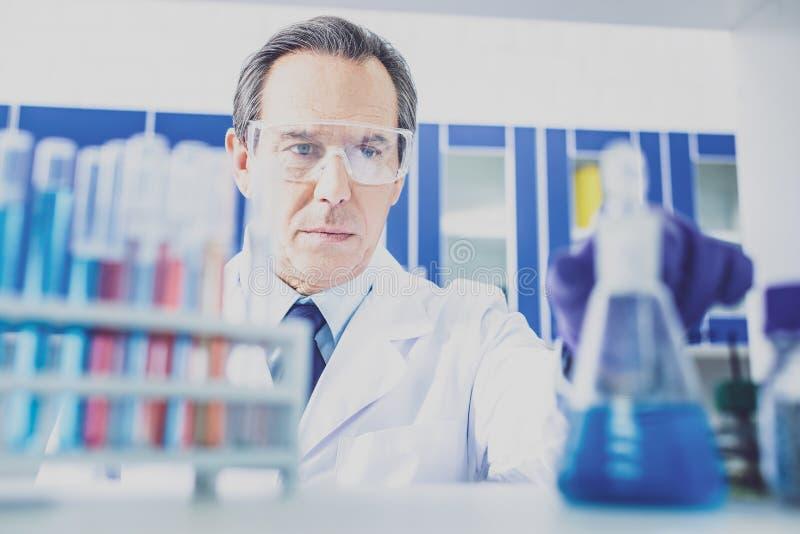 Пожилой химик нося голубые перчатки работая на исследовании стоковое фото rf