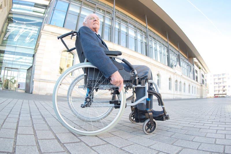 Пожилой человек в здании одного outdose кресло-коляскы большом стоковое фото