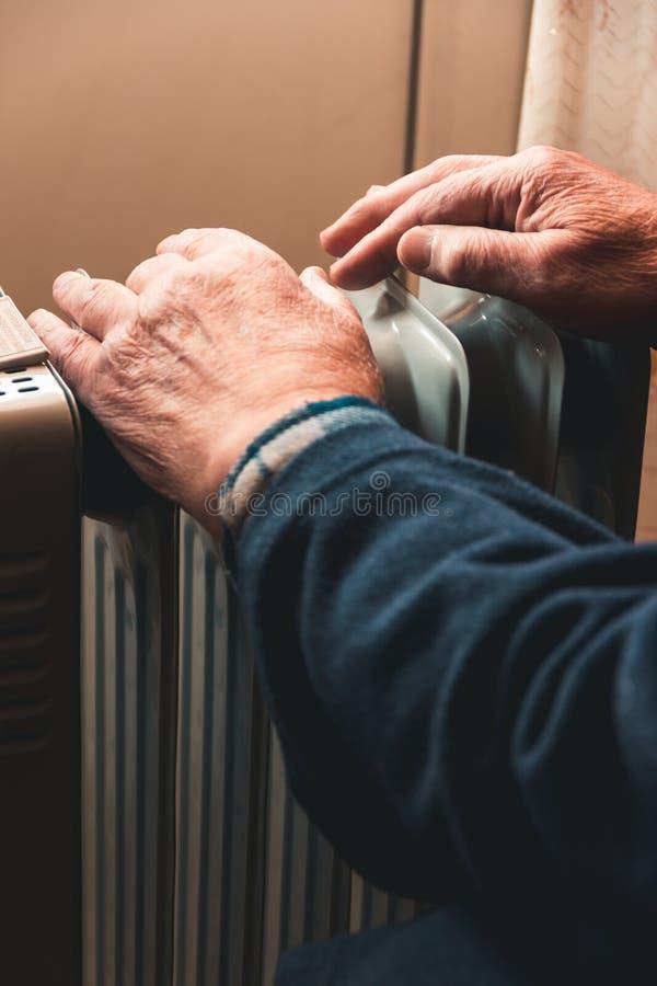 Пожилой человек греет его руки над электронагревателем В мертвом сезоне, центральное отопление задержано стоковые фото
