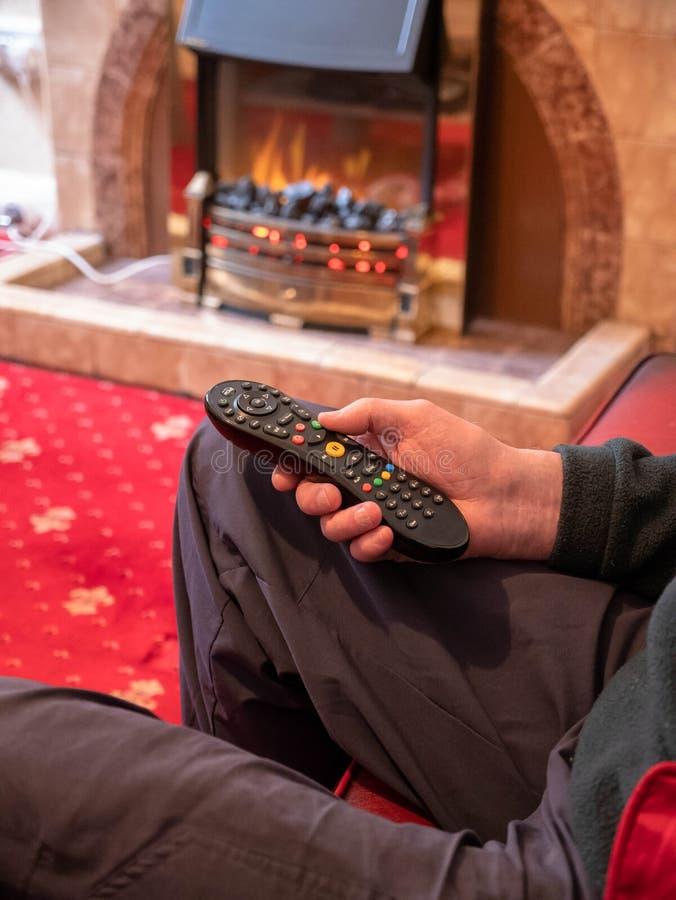 Пожилой человек живя самостоятельно, с дистанционным управлением ТВ в руке стоковое изображение