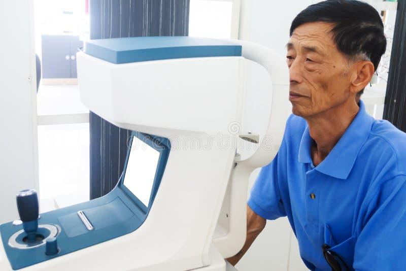 Пожилой человек имея глаза hes быть расмотренным глазным врачом на испытывая инструменте в современной клинике стоковое фото