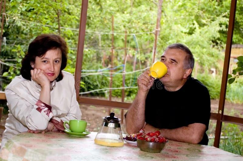 Пожилой человек и женщина выпивают чай на outdoors. стоковые изображения