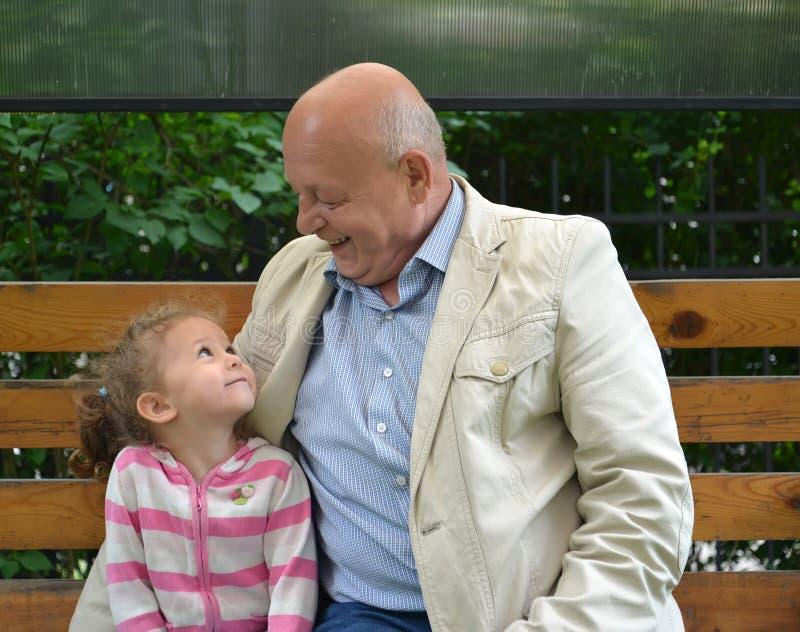 Пожилой человек и маленькая девочка с улыбкой смотрят один другого стоковые фотографии rf