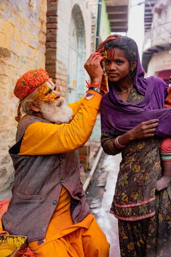 Пожилой человек красит символы используя краску золота на лоб  стоковые фотографии rf