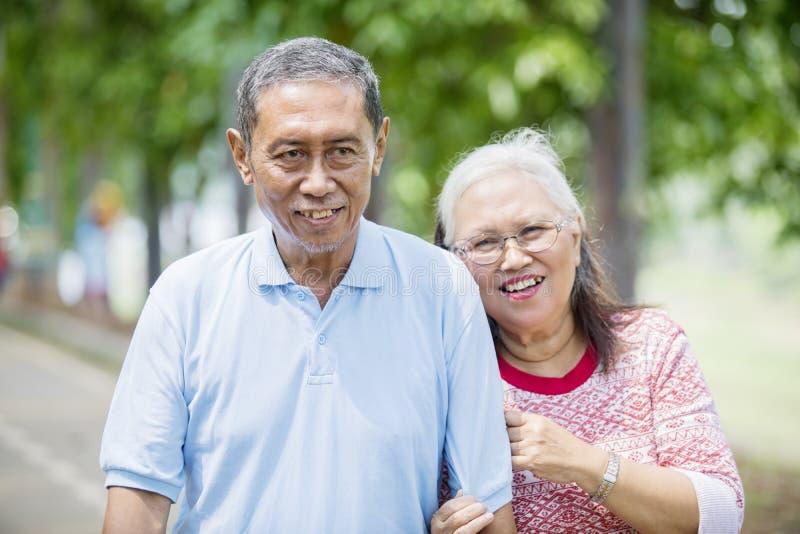 Пожилой человек обнятый его женой на дороге стоковые изображения