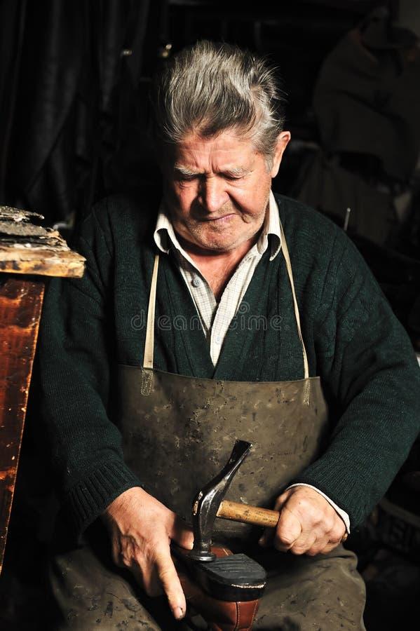 Пожилой человек, ремонтировать shoemaker стоковые фото