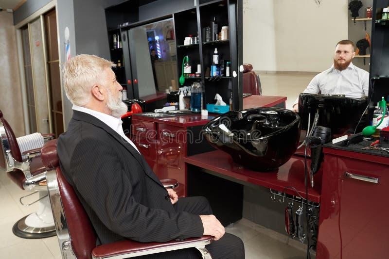 Пожилой человек смотря отражение в зеркале парикмахерскаи стоковое фото rf