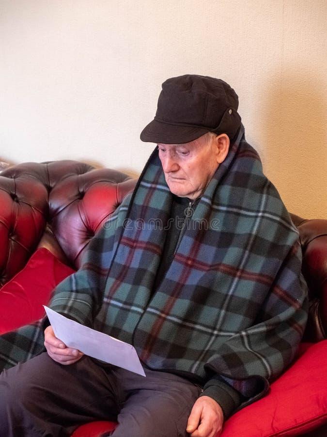 Пожилой человек с потревоженным взглядом и счет в руке стоковое изображение