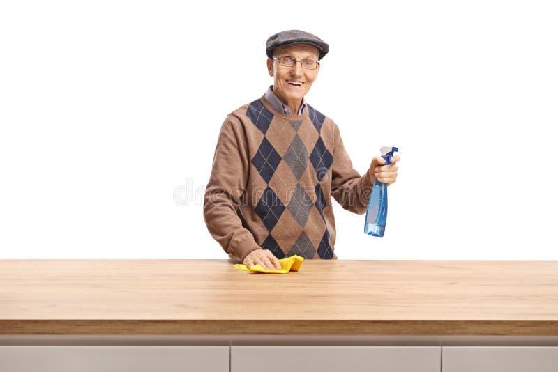 Пожилой человек с тканью и очищая брызгами стоя за деревянной стойкой и усмехаясь на камере стоковые фото