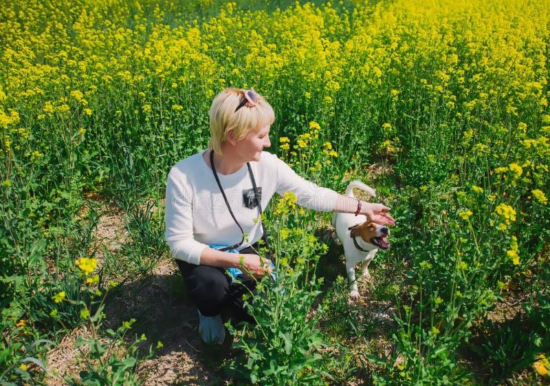 Пожилой штриховать женщины ее поднимает Рассела домкратом на поле рапса стоковые фото