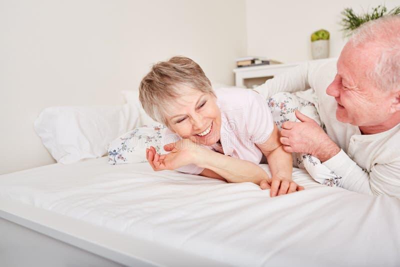 Пожилые гражданины в кровати имея потеху стоковое фото