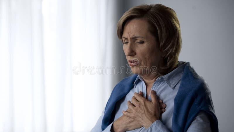 Пожилые дама имея симптомы приступа астмы, трудные к дыханию и боли в комоде стоковые фото