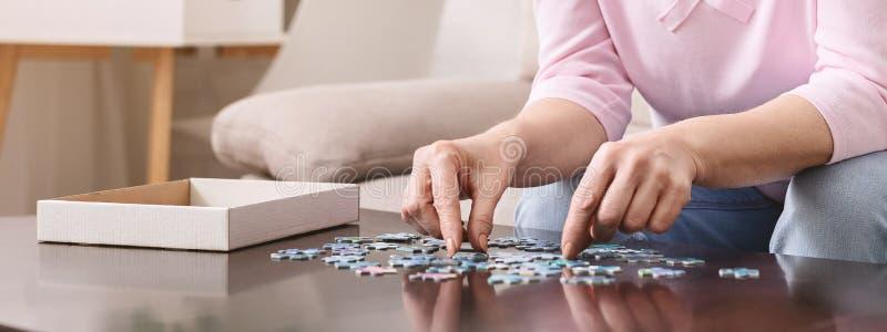 Пожилые женские руки пробуя соединить части мозаики стоковые изображения