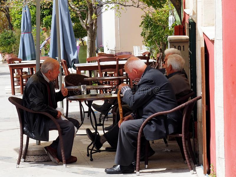 Пожилые люди выпивая кофе в ираклионе Греции стоковое фото