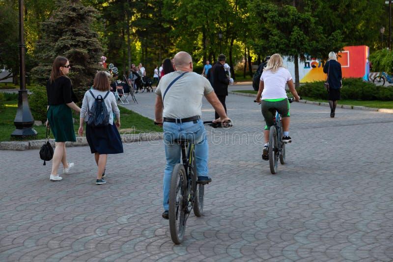 Пожилые люди и женщины пар едут велосипеды во время прогулки в парке среди большое количество людей в выходные дни на теплом стоковое изображение rf