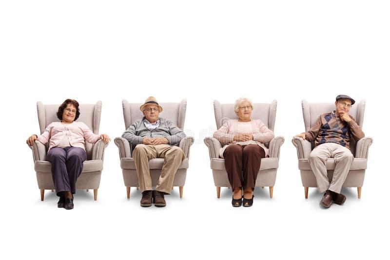 Пожилые люди и женщины сидя в кресле и смотря кулачок стоковое фото rf