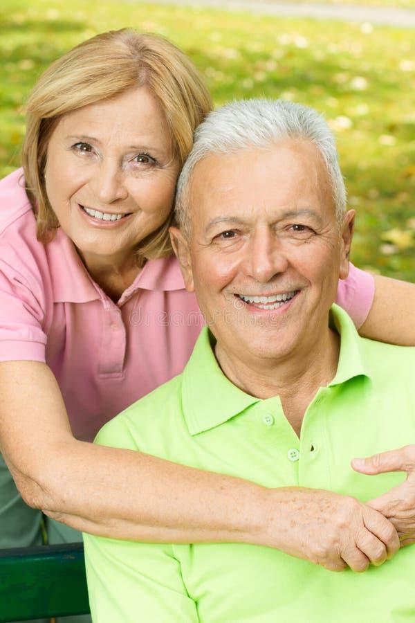 пожилые люди обнимая женщину счастливого человека возмужалую стоковые изображения