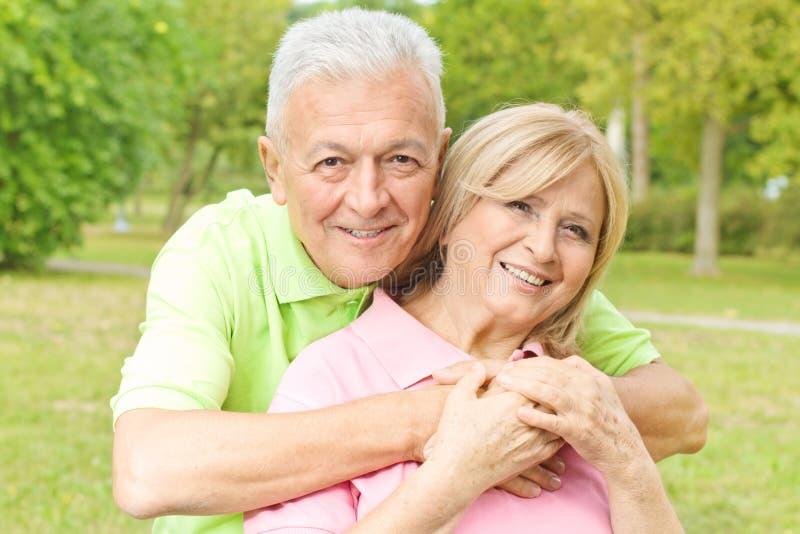 пожилые люди обнимая счастливую женщину старшия человека стоковые изображения