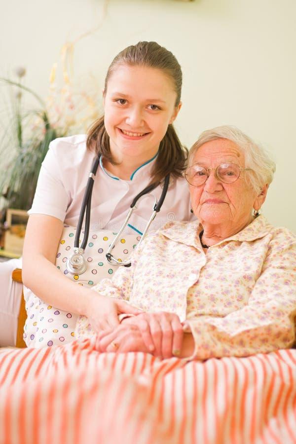 пожилые люди помогая больной женщине стоковое изображение rf
