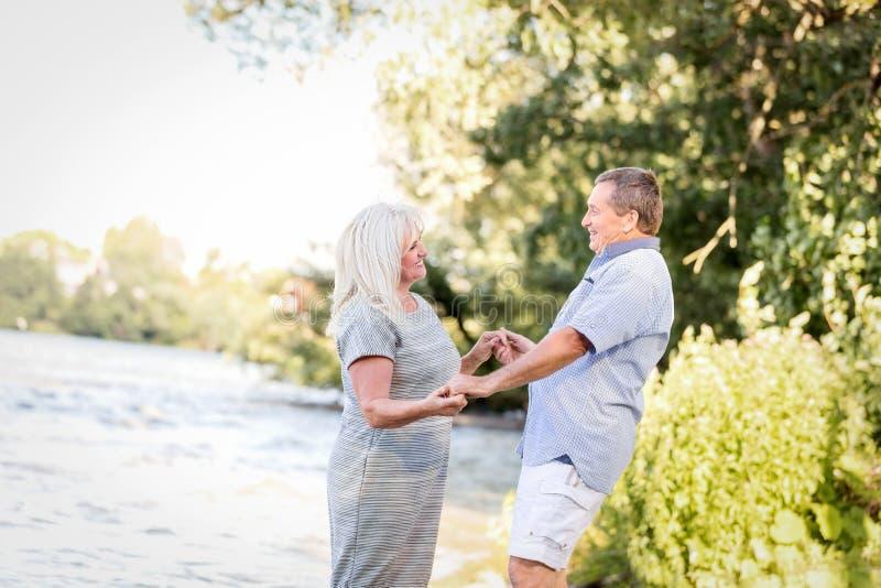 Пожилые пары держа руки озером стоковое изображение