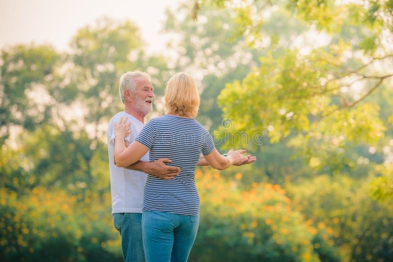 Пожилые пары ослабляя в саде на заходе солнца Любовь пар концепции старшая стоковые фото