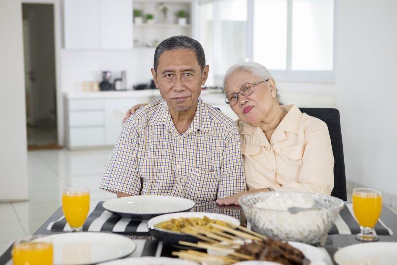 Пожилые пары сидя перед обеденным столом стоковое изображение rf
