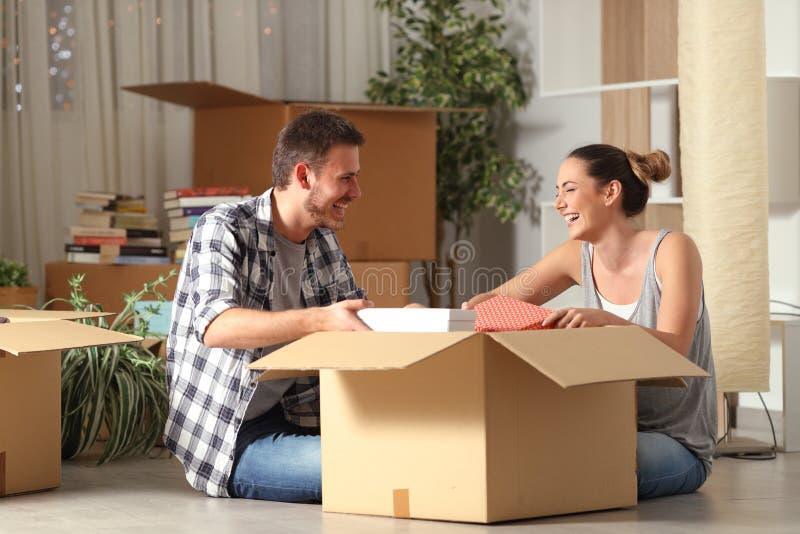 Пожитки счастливых пар смеясь unboxing двигая дом стоковые изображения rf