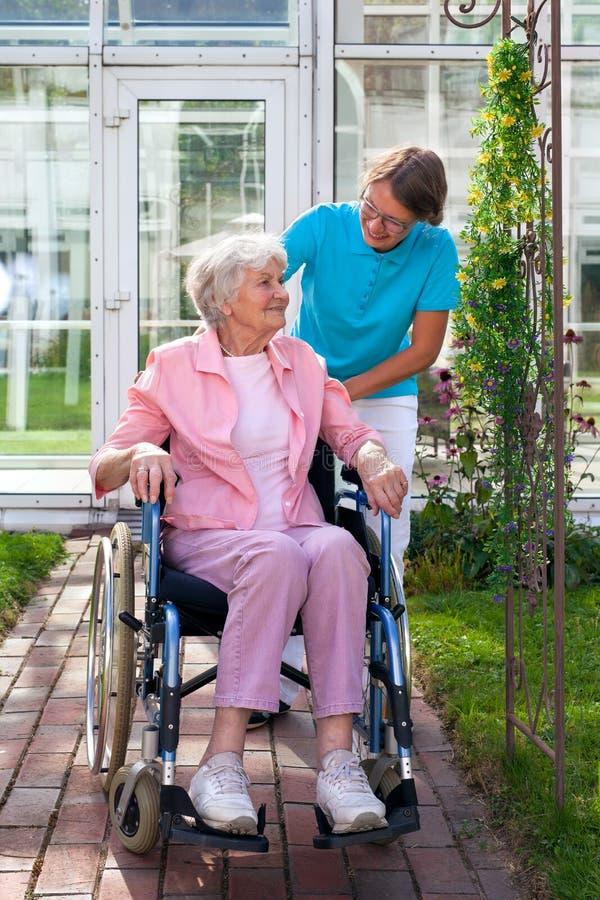 Пожилая дама в кресло-коляске с ее человеком осуществляющим уход стоковое изображение rf