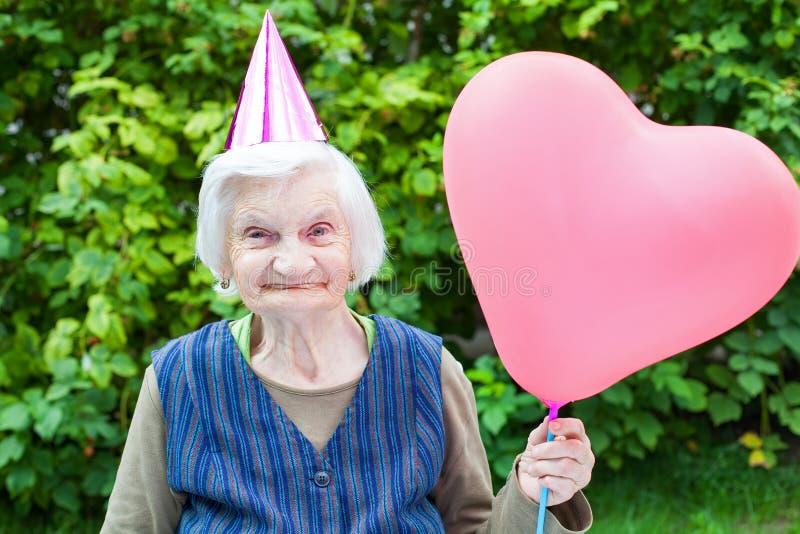Пожилая дама держа воздушный шар сердца форменный стоковая фотография rf